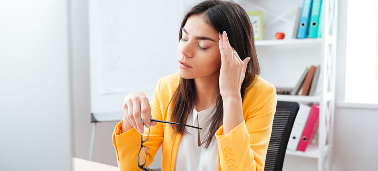 Woman at desk with head pain